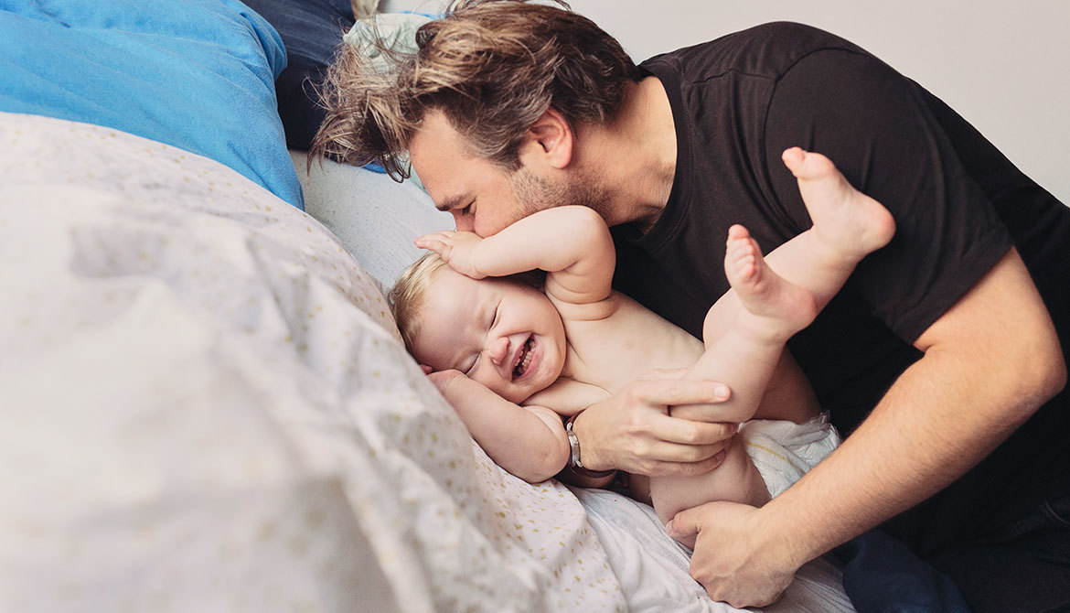 Bambo Nature only additive needed is love, father kissing baby on bed